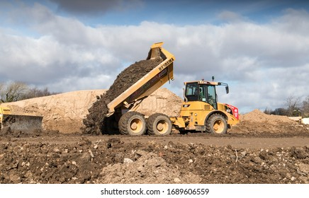 Peterlee / Great Britain - March 9, 2020 : Industrial dumper truck moving tipping earth on a construction site
