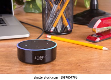 PETERSBURG, ILLINOIS-April 28, 2018: Amazon echo dot, a hands free voice controlled device that connects to the Alexa voice service on a wooden desktop