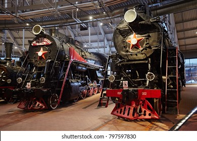 Petersburg, Russia - December 2017: Two old black steam trains at the railway station. Front view. Restored locomotive in retro style. Museum of Railways.