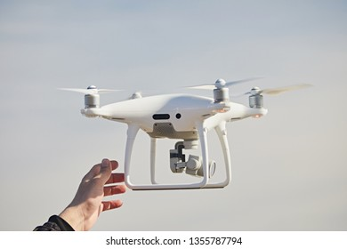 Petersburg, Russia - May 2018:  A man's hand catches a white drone quadrocopter DJI Phantom 4 Pro in the sky. Landing to man
