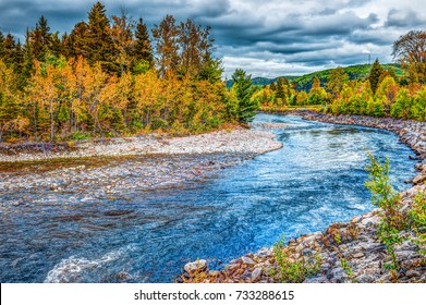 Petit Saguenay river in Quebec, Canada during autumn with curve with orange foliage and blue water