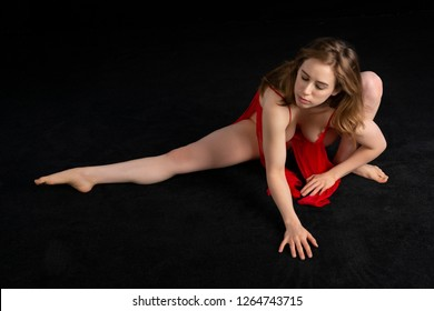 Petite athletic brunette dressed in red negligee