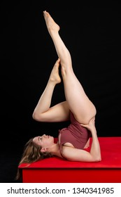 Petite athletic brunette stretching in a purple bodysuit
