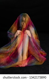 Petite athletic brunette wrapped in sheer rainbow tulle