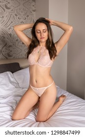 Petite young brunette in bed in pink lingerie