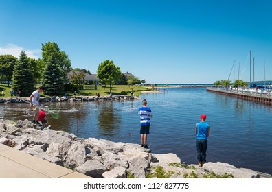 Petosky, Michigan - June 21, 2018: Young anglers fishing in the Bayfront Park on the shore of Lake Michigan in Petosky on Upper Michigan Peninsula