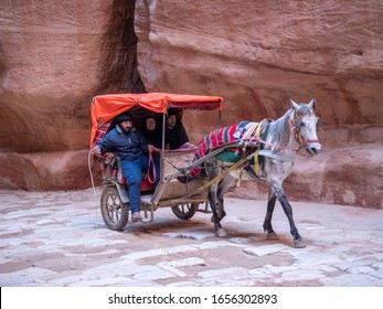 Petra, January 2020,  Jordan: Tourists in a  tour on a horse cart along The Siq in Petra