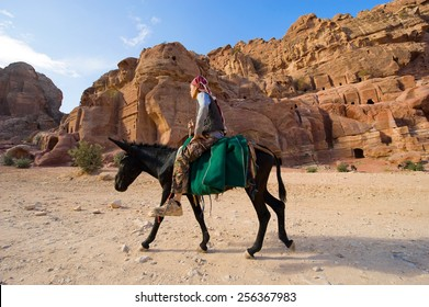 PETRA, JORDAN - 12OCTOBER, 2014: A man is riding on the back of a donkey in Petra in Jordan