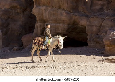 PETRA - JORDAN  25 December 2015: Arab boy riding a donkey in Petra Jordan