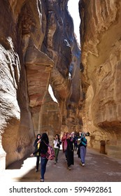 PETRA, JORDAN - APR 2, 2015: Tourists walking in Siq canyon in Petra. Petra's temples, tombs, theaters and other buildings are scattered over 400 square miles. UNESCO world heritage site