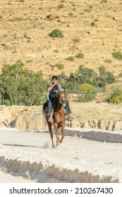 PETRA, JORDAN - APR 29, 2014: Unidentified lman rides a horse in Petra, the capital of the kingdom of the Nabateans in ancient times. UNESCO World Heritage
