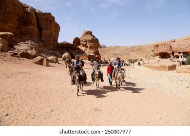 PETRA, JORDAN- APRIL 09, 2014: Tourists with Bedouins visiting the ancient ruins of Petra on donkeys, Jordan
