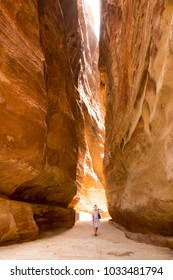 PETRA, JORDAN - APRIL 25, 2016: A narrow passage between steep rock formations in the siq at Petra the ancient City Al Khazneh in Jordan lit by the sun