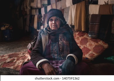 Petra, Jordan, Asia - February 18 2019: Local senior woman covered in traditional bedouin clothes in tent interior looking into camera, cooking bedouin tea, in desert of Petra, Jordan