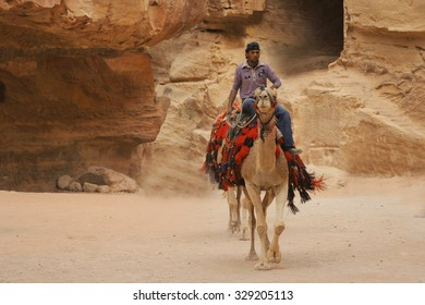 Petra, Jordan - CIRCA October 2009 - Man riding camel through ruins of Petra