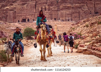 PETRA / JORDAN - MAY 04, 2018 : Bedouin men and their camels at the ancient ruins of Petra.
