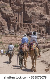 PETRA, JORDAN - MAY 07, 2015: Tourists riding camels and donkeys, circulate along the narrow valley trails, where the stone city is located