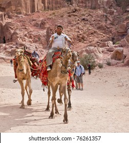 PETRA, JORDAN - NOV 24: Unidentified Bedouin with camels on ancient roadway on November 24, 2010 in Petra, Jordan. Petra is a UNESCO World Heritage Site since 1985.