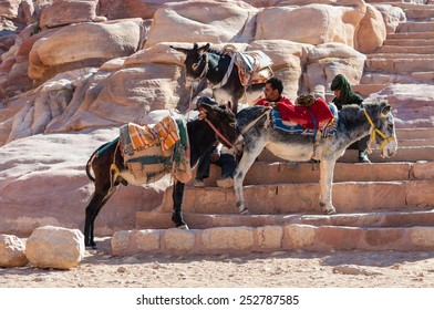 PETRA, JORDAN - NOVEMBER 20:  Arabian men sitting on stone steps and waiting for tourists in the ruins of ancient town Petra at November 20, 2010 in Petra, Jordan. Three donkey standing around them.