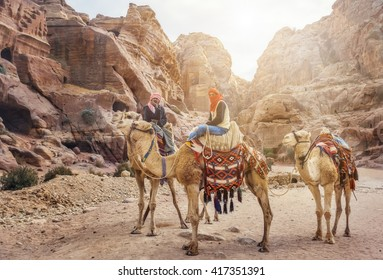 PETRA, JORDAN - NOVEMBER 22, 2007: Unidentified local Bedouin guided on camels near Royal tombs.