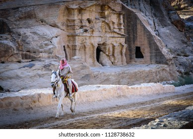 Petra, Jordan - November 28 2017: Bedouin man riding a white horse with ancient building carved in the rock in the background nearby the archaeological area of the Treasury, UNESCO World Heritage Site