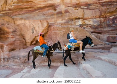 PETRA,  JORDAN - OCT 12, 2014: Two donkeys with his owner and a tourist are climbing up the long stairs to the 'Ad Deir' Monastery in Petra in Jordan