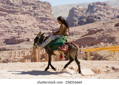PETRA,  JORDAN - OCT 12, 2014: A donkey with his owner on his horseback riding in Petra in Jordan