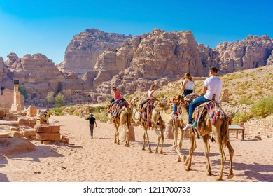 PETRA, JORDAN - OCTOBER 13, 2018: Tourists riding a camels at the ancient ruins of Petra.