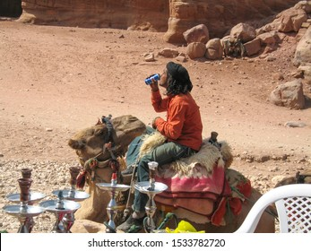 Petra, Jordan - October 17 2007: Camel watches Bedouin man drink Pepsi on the archaeological site, built by the Nabataeans.  Archaeology, history concepts.