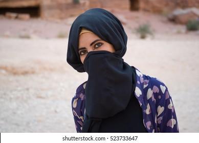 Petra, Jordan - October 26, 2016: Close up of a Bedouin girl with hidden face behind veil posing at camera