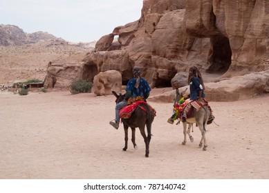 Petra, Jordan - October 26, 2016: Beduin men riding donkeys in the ancient Nabatean city of Petra, Jordan