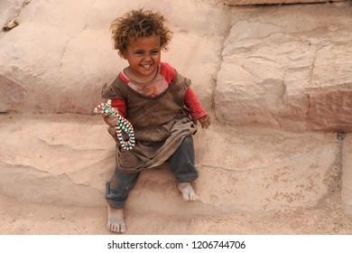 Petra, Jordan - September 30th, 2018: a bedouin littlegirl selling necklaces in the lost city of Petra, in Jordan