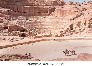 PETRA, JORDAN-MARCH 7, 2018: Ruins of an ancient amphitheater and three tourists and one drover with two camels in Petra, Jordan