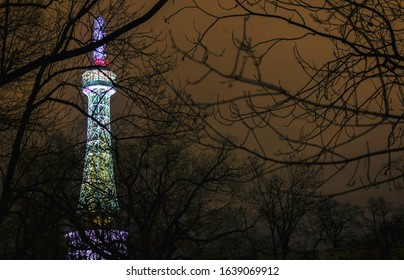 """Petrin lookout tower from 19th century at night. Tower at Petrin hill in Prague with silhouettes of tree branches. In Czech: """"Petrinska rozhledna"""". Sometimes it is called the Prague Eiffel Tower."""