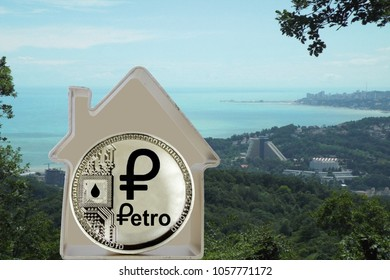 Petro coin in a metal house on a sea cost background. Rent or buy a house for PTR.