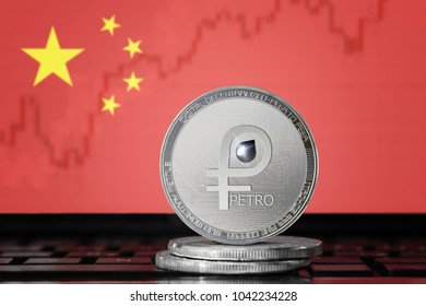 PETRO (PTR) cryptocurrency; coin el petro on the background of the flag of China (PRC); national Venezuela cryptocurrency