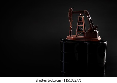 Petrochemical industry, big oil and drilling for fossil fuel concept with a oil derrick on oil barrels against black background with dramatic lighting and copy space