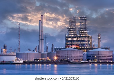 Petrochemical industry next to a river with a dramatic cloudy sky at twilight, Port of Antwerp, Belgium.