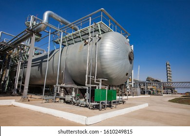 Petrochemical industry. Oil refinery plant in desert. Heat exchanger and pipelines on distillation towers and blue sky background. Zhanazhol  oil deposit, Kazakhstan.