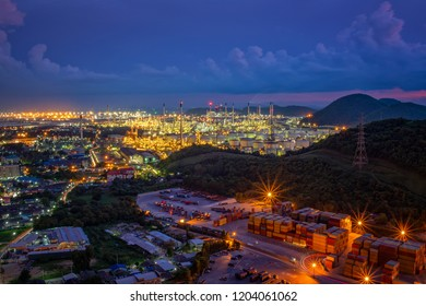 Petrochemical oil refinery plant with chemical tank and equipment pipeline near seaport at the night light cityscape around urban