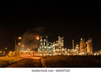 Petrochemical refinery at night behind a closed fence. Tessenderlo, Flanders, Belgium, Europe