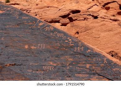 Petroglyphs on a red rock seen during a hike on the Petroglyph Canyon Trail at Valley of Fire State Park in Nevada