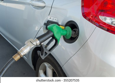 Petrol pump nozzle in car's petrol tank filling it up with petrol at a petrol station. Petrol pump hose is black rubber and nozzle is green. Part of car's tail light can be seen.