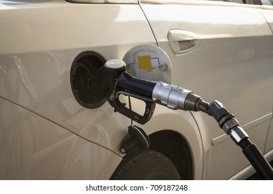 petrol pump nozzle hold by hand with gasoline