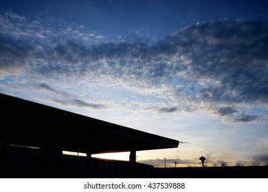 Petrol station with beautiful cloud sky during sunset. Concept of dark object and bright sky.