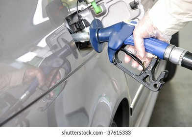 At the petrol station. Closeup of a man's hand using a petrol pump to fill his car up with fuel.
