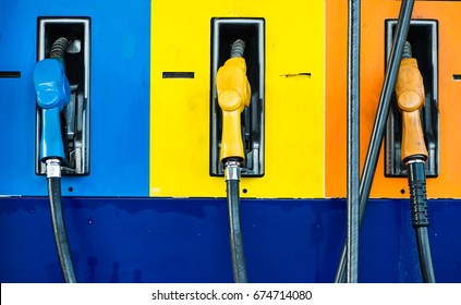 Petrol station has classified type of fuel by color of pump blue yellow and orange