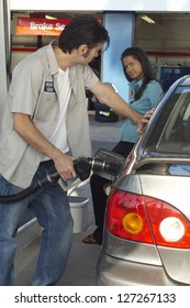 Petrol station worker refueling the car while looking at businesswoman