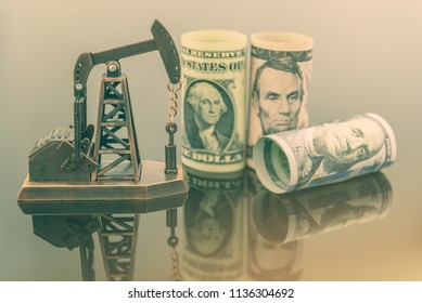 Petroleum, petrodollar and crude oil concept : Pump jack and US USD dollar banknotes, depicts the money received or earned from sales after investment in the development or production of oil industry.