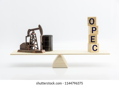 Petroleum, petrodollar and crude oil concept : Pumpjack, oil drum barrel and wood blocks with word OPEC or Organization of Oil Exporting Countries on a seesaw or basic balance scale, white background